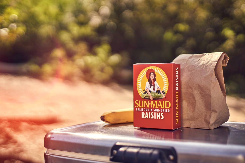 A box of Sun-Maid raisins beside a brown-bag lunch